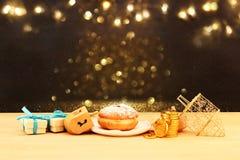 犹太假日光明节的图象与木dreidels & x28的; 转动的top& x29;并且在桌上的多福饼