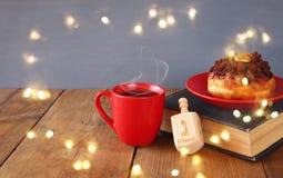 犹太假日光明节的图象与油炸圈饼、木抽陀螺、杯子热巧克力和旧书的 库存照片