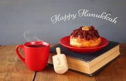 犹太假日光明节的图象与油炸圈饼、木抽陀螺、杯子热巧克力和旧书的 免版税库存照片