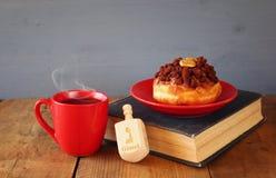 犹太假日光明节的图象与油炸圈饼、木抽陀螺、杯子热巧克力和旧书的 免版税库存图片
