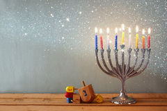 犹太假日光明节的图象与menorah (传统大烛台)和木dreidels (抽陀螺)的 免版税库存照片