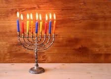 犹太假日光明节背景的低调图象与menorah灼烧的蜡烛的在木背景