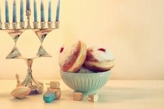 犹太假日光明节背景的图象与传统spinnig上面、menorah & x28的; 传统candelabra& x29;并且多福饼 免版税库存图片