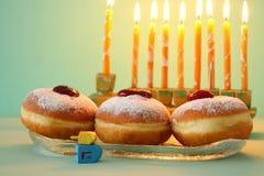 犹太假日光明节背景的图象用多福饼和menorah & x28;传统candelabra& x29;