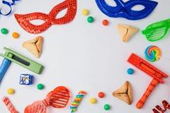 犹太假日普珥节概念与hamantaschen曲奇饼、狂欢节面具和发出大声音的人在白色背景 免版税图库摄影