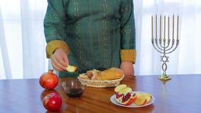 犹太妇女采取切片苹果并且浸洗它在犹太新年的蜂蜜 股票视频