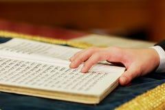 读犹太摩西五经的男孩的手在成人仪式01威严2015年 免版税图库摄影