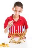 犹太男孩点燃Menorah 免版税图库摄影