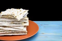 犹太Matzah面包照片在陶瓷板材的在蓝色木桌上 Matzah为犹太逾越节假日 有选择性的s 库存图片