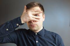 犹豫或害怕 人通过他的手指看 库存照片