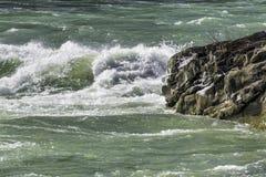 狂放和浪潮起伏的河当前打破在岩石,蓝绿色wa 库存图片