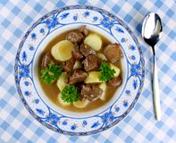 狂放的墩牛肉用土豆、调味汁和匙子在蓝色板材 库存图片