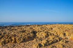 狂放的夏天海洋海滩,葡萄牙 清楚的天空,在沙子的岩石 免版税库存图片