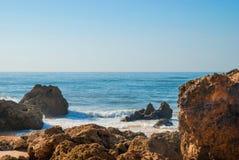狂放的夏天海洋海滩,葡萄牙 清楚的天空,在沙子的岩石 免版税库存照片