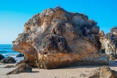 狂放的夏天海洋海滩,葡萄牙 清楚的天空,在沙子的岩石 库存照片