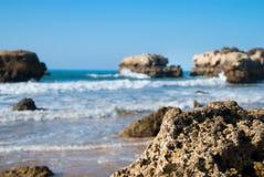 狂放的夏天海洋海滩,葡萄牙 清楚的天空,在沙子的岩石 库存图片