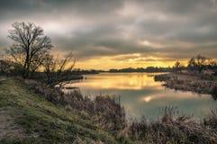 狂放的池塘在与黄色光束的多云早晨 免版税库存照片