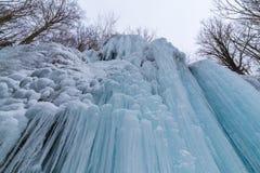 狂放的河、美丽的结冰的瀑布和新鲜的雪在一个山森林里,在一个冷的冬日 免版税库存图片