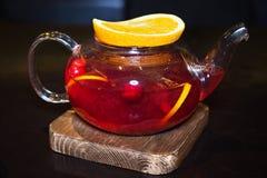 狂放的莓果茶用果子在一个木立场的切片桔子 库存照片
