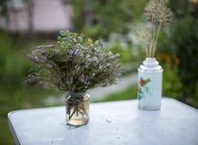 狂放的迷迭香花花束在户外桌上的 免版税库存照片