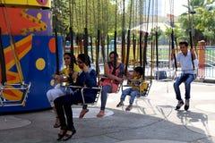 狂欢节乘驾摇摆享受狂欢节的椅子人在暑假乘坐 库存图片