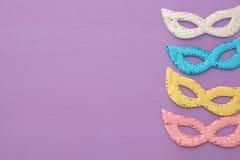 狂欢节党与五颜六色的粉红彩笔、金子、银和蓝色面具的庆祝概念在紫色木背景 顶视图 免版税库存图片