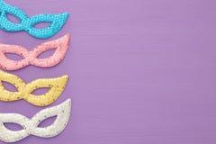 狂欢节党与五颜六色的粉红彩笔、金子、银和蓝色面具的庆祝概念在紫色木背景 顶视图 免版税库存照片