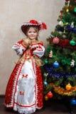 狂欢节服装的小女孩在圣诞树附近 库存图片