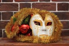 狂欢节面具和圣诞节装饰在砖墙附近 免版税图库摄影