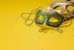 狂欢节面具和小珠在黄色背景 文本的空间 免版税图库摄影