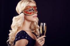 狂欢节面具的美丽的白肤金发的妇女,与杯香槟 免版税库存照片
