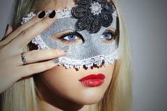 狂欢节面具的美丽的白肤金发的少妇 化妆舞会 红色背景秀丽黑色女孩查出的嘴唇 修指甲 免版税库存照片