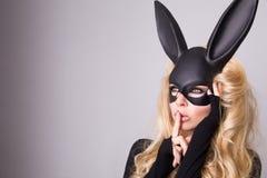 狂欢节面具舞厅兔子的美丽的金发的少妇与长的耳朵肉欲性感在一件黑礼服,站立defian 免版税库存图片