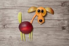 狗做用果子在木背景 图库摄影