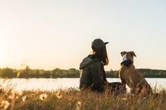 狗和她的所有者由湖坐在日落 库存图片
