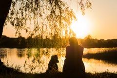 狗和所有者在湖日落的 免版税库存图片