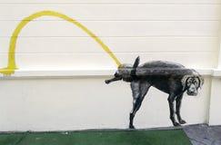 狗在墙壁的小便绘画 免版税库存图片