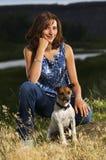 狗女孩她的宠物坐年轻人 免版税库存图片