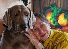 狗愉快的高级妇女 免版税库存图片