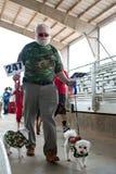 狗所有者和长卷毛狗在节日的两件穿戴卡莫衬衣 免版税库存照片