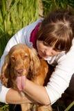 狗拥抱的女孩她的纵向年轻人 图库摄影
