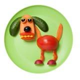 狗由新鲜蔬菜做成在绿色板材 免版税图库摄影