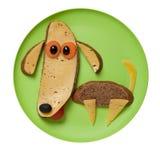 狗由黑面包和乳酪制成在绿色板材 免版税库存图片