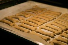 狗的圣诞节曲奇饼在骨头在烤箱的形状烘烤 免版税库存照片