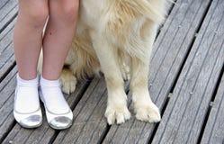 狗的爪子和孩子的脚 免版税库存照片