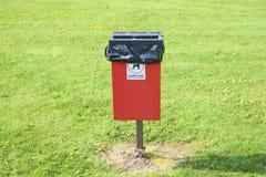 狗poo废物箱袋子在红色容器的环境标志在公园令人鼓舞所有者之后整理 免版税库存照片