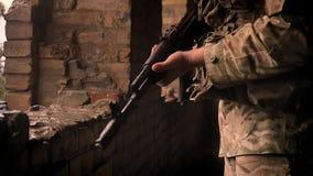 狙击手强的剪影直站和拿着自动炮的伪装的在砖放,大雨外部 股票视频