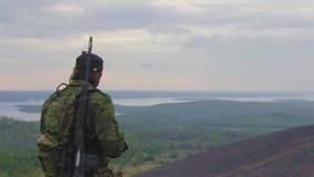 狙击手调查距离并且离开对他的肩膀调整步枪 股票录像