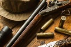 狩猎步枪、弹药、一把刀子和一个盖帽在桌上 库存图片