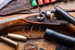 狩猎步枪,子弹带,在一张木桌上的双筒望远镜 库存图片